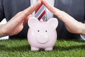 Businessman Sheltering Piggybank — Stock Photo
