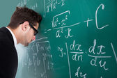 Professor Leaning Head On Blackboard — Stockfoto