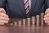 Businessman Protecting Coin Stacks — Stockfoto