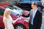 Salesman Handing Key — Stock Photo