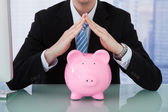 Businessman Protecting Piggy Bank — Stockfoto