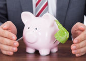 Businessman Shielding Piggybank — Stock Photo