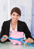 Businesswoman Measuring Piggybank — Stock Photo