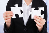Businesswoman Joining Jigsaw Pieces — Stock Photo