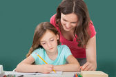 Woman Assisting Daughter In Studying — Stock Photo