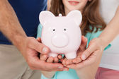 Family hands Holding Piggy Bank — Stock Photo