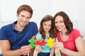 Happy Family Joining Puzzle Pieces — Stock Photo