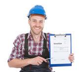 Smiling handyman showing invoice — Stock Photo