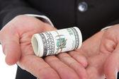Hands holding tied dollar bills — Stock Photo