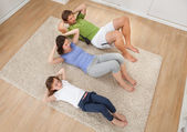 Family Doing Situps On Rug — Stock Photo