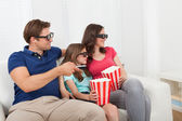 Family in 3D glasses with popcorn — Stock Photo