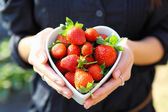 Strawberry in heart shape bowl with hand — Stock Photo