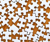 White jigsaw puzzle on wooden background — Stock Photo