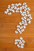 Fragezeichen gemacht von puzzle auf holz-hintergrund — Stockfoto