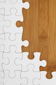 Puzzle on wooden board — Stock Photo