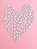 Puzzle made heart shape on pink background — Stock Photo