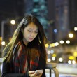 Woman use mobile phone in city at night — Stock Photo