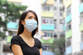 Woman wearing medical face mask in crowded city — Stock Photo