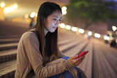 Woman using phone in city at night — Stock Photo
