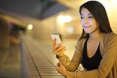 Vrouw met behulp van smartphone in stad bij nacht — Stockfoto