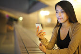 Woman using smartphone in city at night — ストック写真