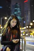 Mujer usar teléfono móvil en la ciudad de noche — Foto de Stock