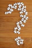 Znak zapytania przez puzzle drewniane tła — Zdjęcie stockowe