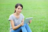 Donna seduta sull'erba con computer tablet — Foto Stock