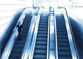 Person in motion on escalator — Stock Photo