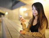 Asian woman using smartphone at night — Stock Photo