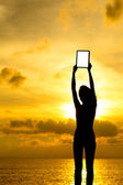 Silhouette der frau holding tablet pc bei sonnenuntergang — Stockfoto