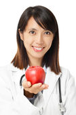 Asian female doctor holding red apple — Stock Photo