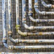 Stock Photo: Series of parallel old pipes on wall