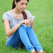 Woman sitting on grass with smartphone — Stock Photo