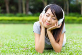 Asian woman listen to song lying on grass — Stock Photo
