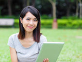 Asian woman holding tablet — Stock Photo