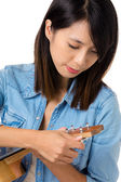 Asian woman tunning ukelele — Stock Photo