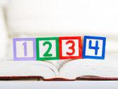 Alphabet block with 1234 on book — Stock Photo