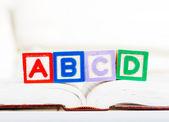 Bloco do alfabeto com abcd no livro — Fotografia Stock