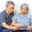 Asian elderly couple using digital tablet — Stok fotoğraf
