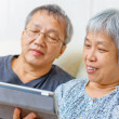 Asian elderly couple using digital tablet — Stock Photo