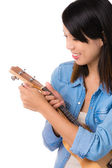 Asian woman tuning ukelele — Stock Photo