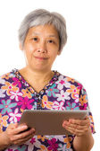 Asian mature woman with digital tablet — Stock Photo