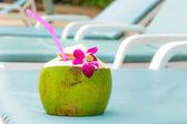 Bain de soleil avec verre de noix de coco — Photo