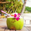 Coconut drink on table beside beach — Stock Photo