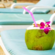 Coconut with drinking straw on beach bench — Stock Photo