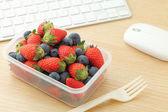 在办公桌的浆果混合午餐盒 — 图库照片