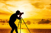 Silhouette of photographer with tripot at sunset — Stock Photo