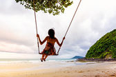 Girl playing the swing on beach — Stock Photo