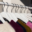 Clothes hang on a shelf in a store — Stock Photo